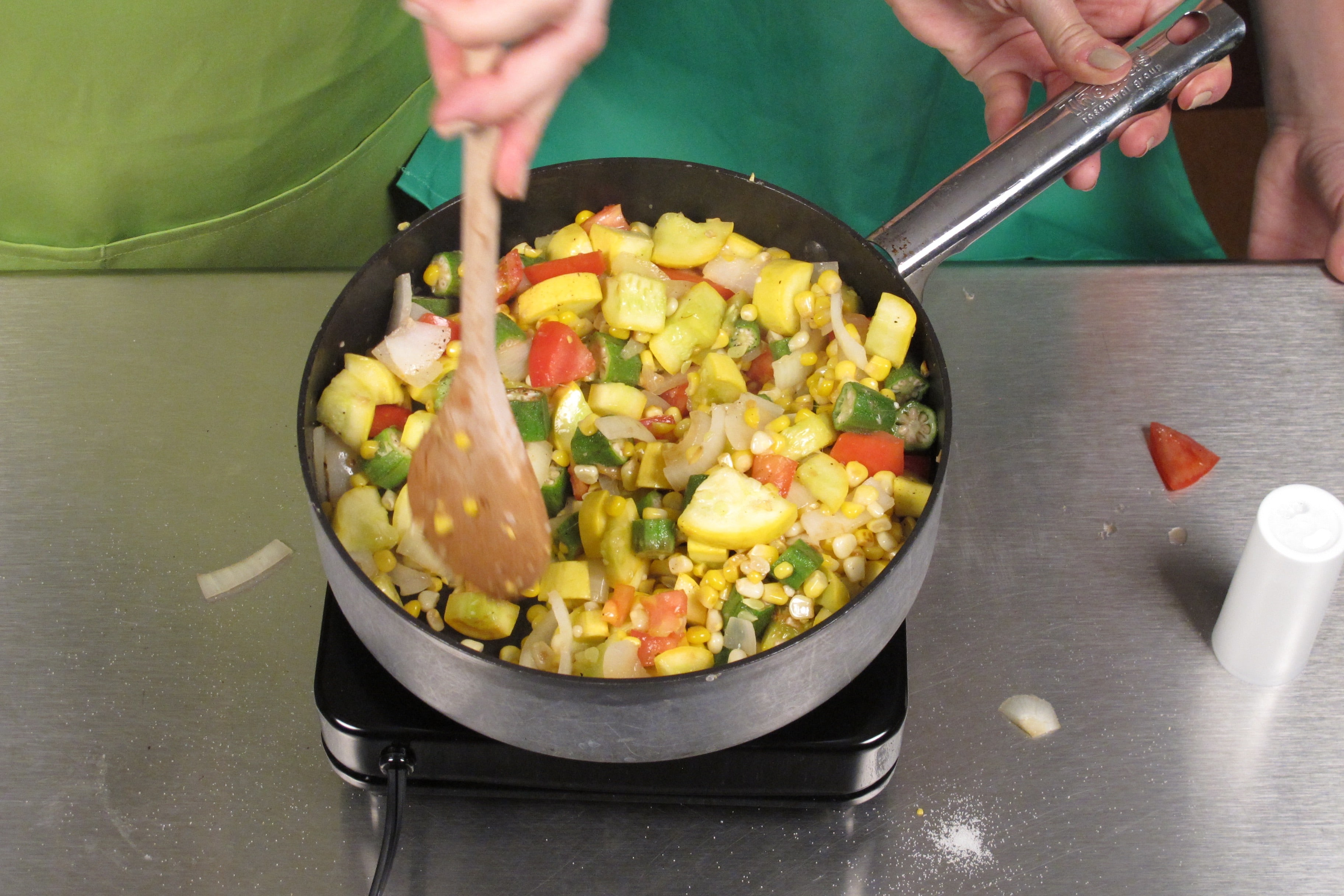 In a large skillet over medium heat, cook oil, onion, corn, squash, and okra for 5 minutes.